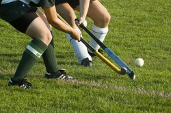 Two girls battle for control of the ball in a field hockey game.
