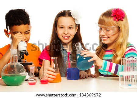 Two girls blond and brunet and black boy, with microscope, test tubes and flasks conducting experiments, isolated on white