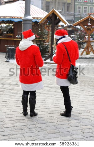 Two girls dressed as Santa Claus on a city street