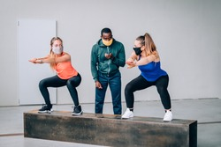 Two girls exercising with a personal trainer at the gym with protective mask in pandemic period of covid19 - Two fit young girls in a gym doing squats with their afro american trainer