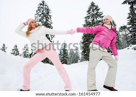 Two girls friends playing games holding their hands together and pulling in different directions, having fun during a winter day out in the snow mountains, outdoors.