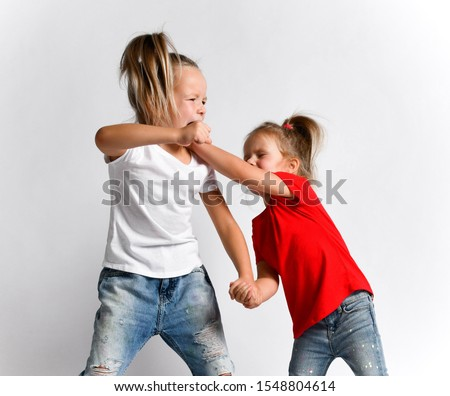 Two girls friends, sisters in jeans and t-shirts are fighting, crying hurt each other, abuse. Younger hits fight back elder. Bad attitudes, family conflict, human relations concept