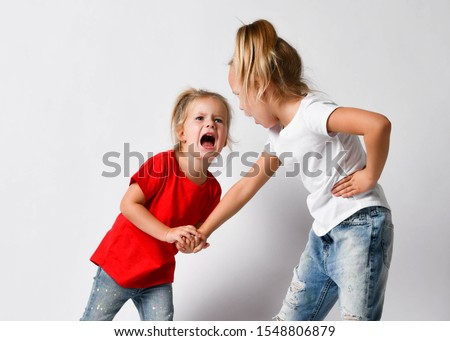 Two girls friends, sisters in jeans and t-shirts are fighting, crying, yelling, argue, hurt each other, abuse on white. Bad attitudes, family conflict, human relations concept