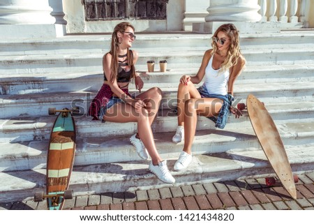 Two girls girlfriends, sitting on the stairs in summer in city, talking talk, happy laugh and smile, skateboard, cups of coffee, beautiful and tanned figures. Concept best friends girlfriend. #1421434820