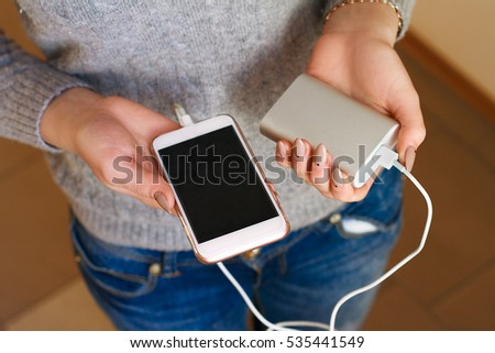 Two girls hands hold of the phone and charger. Powerbank and smartphone in girl's hands. Energy charger power bank smart phone. Still life modern digital concept.