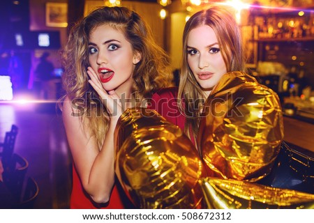 Two girls, happy stylish friends  celebrating new year or birthday  party holding gold stars balloons, surprised faces.  Fashion  elegance  women enjoying time together.