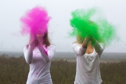 two girls have fun with the paint holi