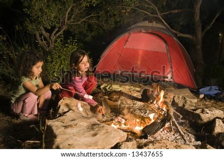 two girls having fun at a bonfire eating marshmallow