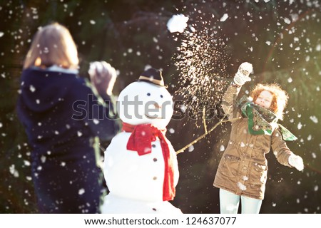Two girls having snowball fight. One of them throwing snowball is in focus, motion blur