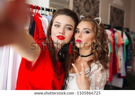 Two girls  holding camera and taking self portrait, photo by cell phone. Young models with make up in fashionable clothes making photo together, showing peace by fingers. #1105866725