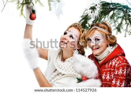 two girls holding christmas ball. Isolated
