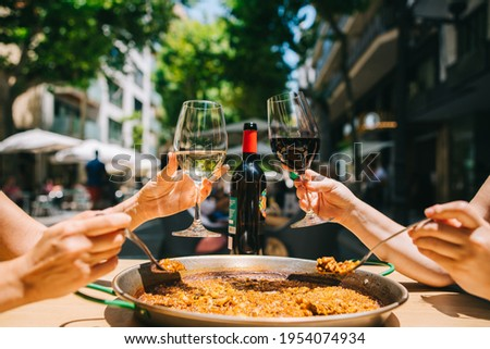 two girls holding drinks wine start eating paella with seafood and squid at a table in a restaurant