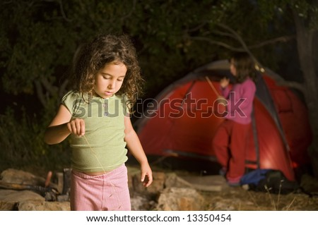 two girls in a camp site by night