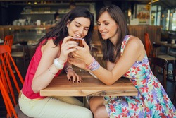 Two girls in a coffee shop, smiling, gossiping, drinking coffee, looking at smartphone