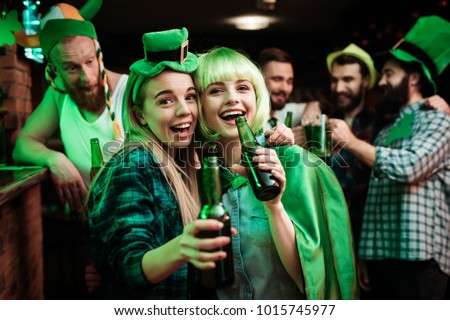 Two girls in a wig and a cap are photographed in a bar. They celebrate St. Patrick's Day. They are having fun.