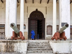 Two girls in blue burqa walking against old door and two powder canon's in front of white building. Zanzibar, Tanzania.