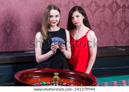 Two girls in casino around roulette with card batch #541379944