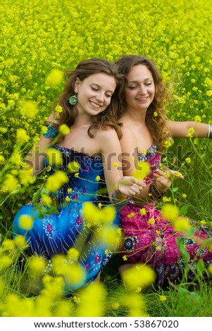 Two Girls  in field of yellow flowers of rapeseed