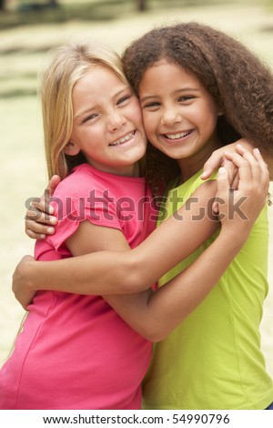 Two Girls In Park Giving Each Other Hug