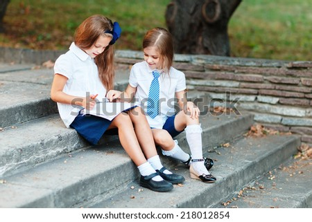 Two girls in school uniform studying at the park