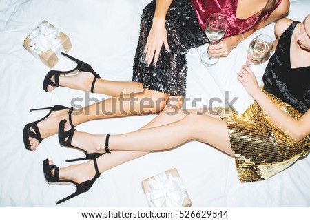 Two girls in shiny skirts with champagne and gifts lie on the bed