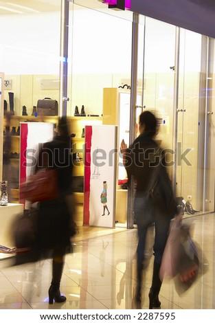 Two girls in shopping center near a show-window of shop.