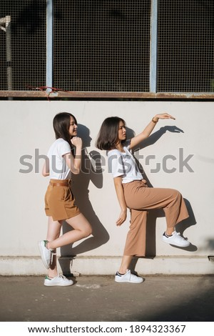 Two girls in white t-shirt and brown pants do the silly act together in the sunlight at the wall. Stock photo ©