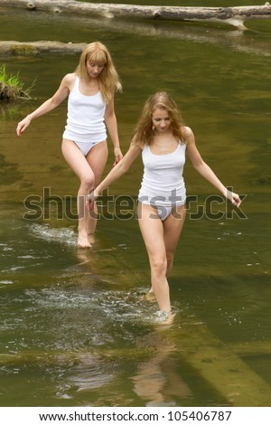 Two girls in white t-shirts are on the green water.