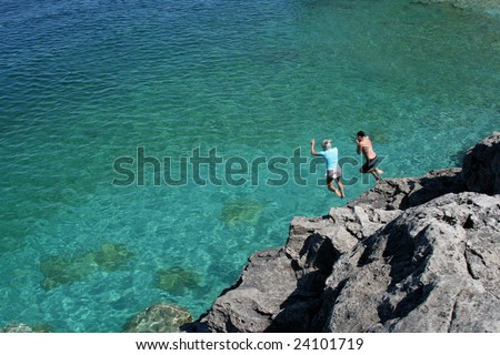 Two girls jumping off the cliffs at Cypress Lake National Park, in Ontario, Canada.