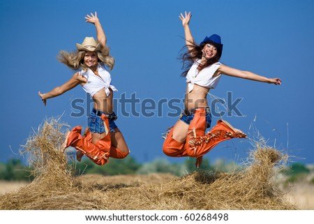Two girls jumping on haystack. Young women in costumes of cowboys outdoors