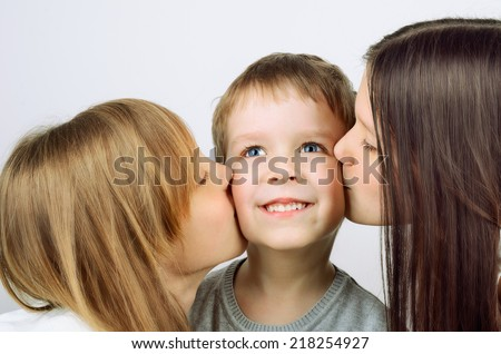 two girls kissing little cheerful boy. horizontal format