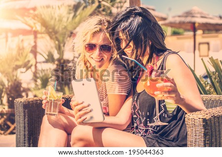 Two girls looking at phone outdoor drinking cocktails