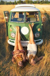 two girls lying in the grass in front of an old minibus
