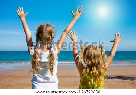 two girls near a sea pulling his hands to heaven