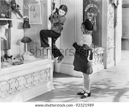Two girls on the street with one climbing on a display window