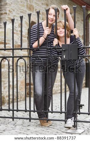 Two girls peeking through closed gate