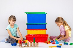 Two girls play toys, in the middle are boxes with toys