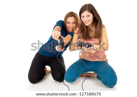 Two girls play video games on the joysticks