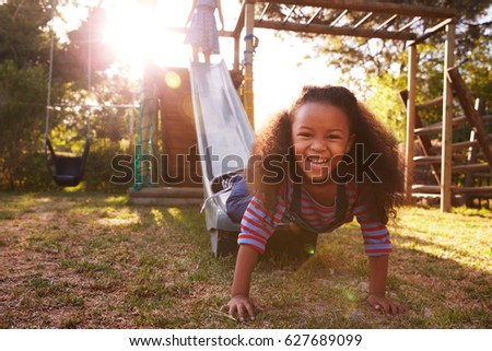 Two Girls Playing Outdoors At Home On Garden Slide Stock photo ©