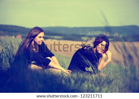 Two girls playing with a cat on the meadow