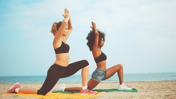 two girls practicing yoga on beach. afro hair girl and blond girl training yoga meditation together on the sea side.