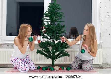 Two girls preparing for winter holidays - stock photo