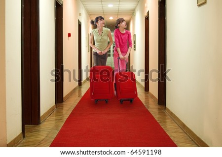 Two girls push luggage in hotel hall and looking at number of rooms