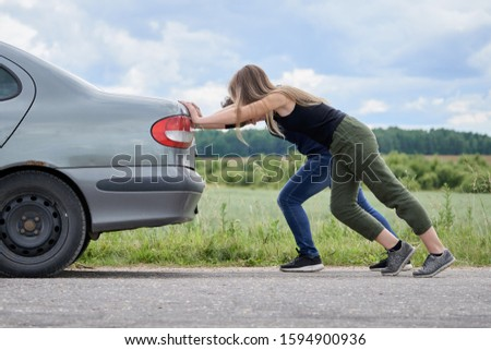 Photo of  Two girls pushing their car which has run out of petrol along a country road in summer day