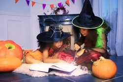 Two girls read wizard book in Halloween witch costumes cast a spell with magic wand holding sit by fireplace