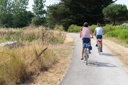 two girls ride bike in path bikeway in Ile de noirmoutier island in France Vendée