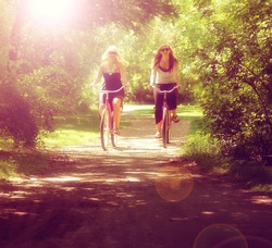 two girls riding bikes on a path in a park full of trees toned with a retro vintage instagram filter effect app or action