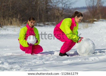 Two girls rolling a huge snowball in wintertime
