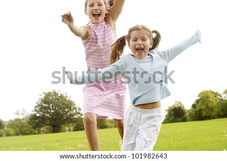 Two girls running towards the camera in the park, smiling.