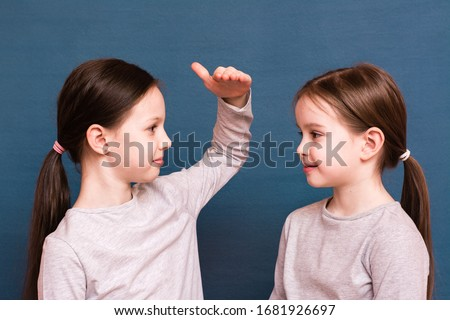 Two girls sisters compare each other's growth with a palm on a blue background Photo stock ©